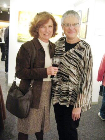 Customer Barbara Apking sips red wine while chatting with Diane Hanson, proprietor of Hanson's Fine Arts and Craft in Bearden