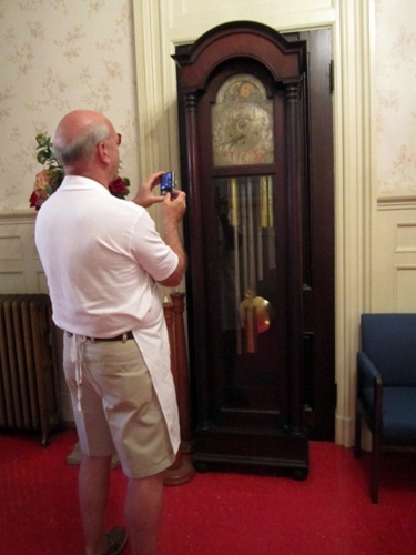 Bruce Anderson takes a picture of a very interesting clock in the entry way.
