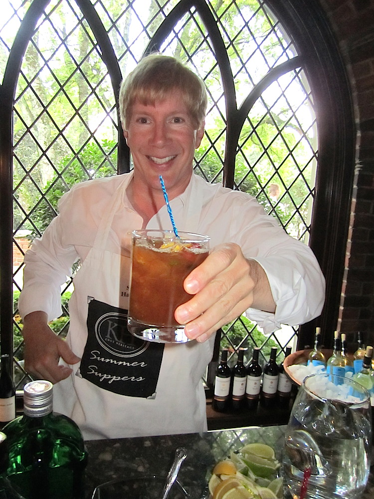Steve Hackney, one of the Summer Supper hosts, offers a Pimm's Cup to guests at the home of Penny Lynch and Kimbro Maguire.