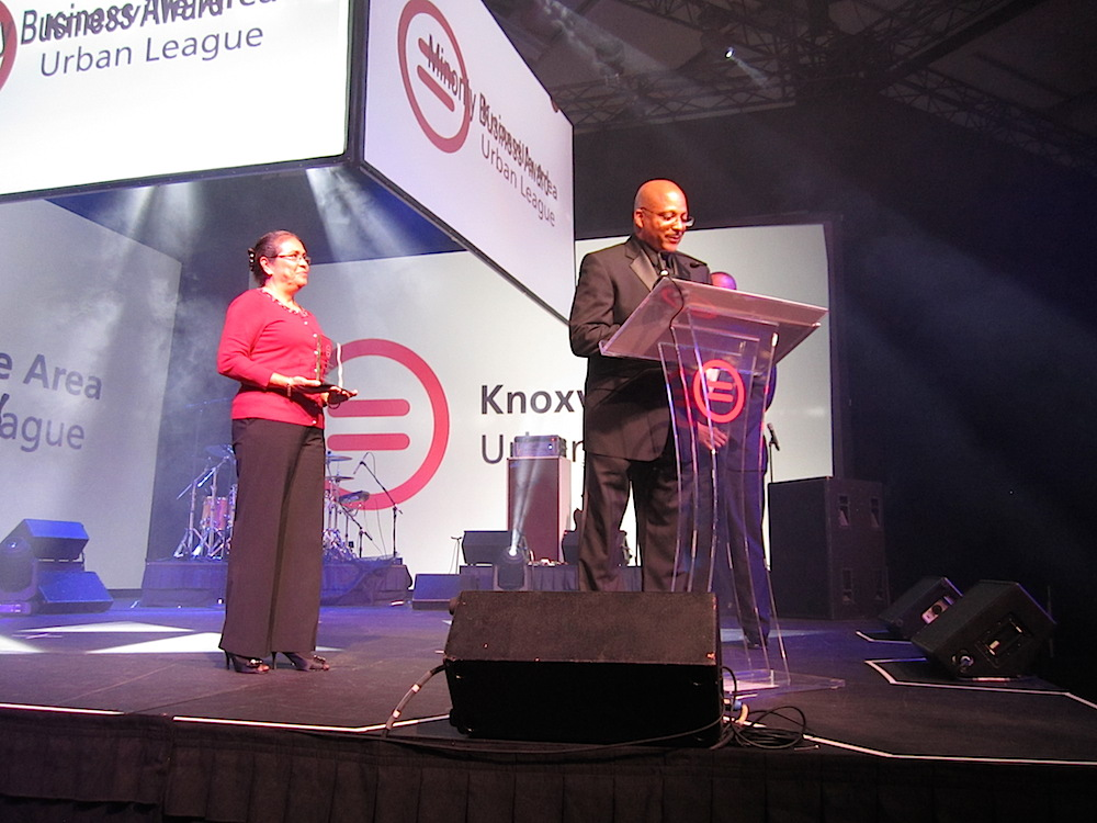Urban League Board Member Rosa Mar holds the Minority Business Award as Mark Deathridge, president of CEO of East Tennessee Mechanical Contractors, delivers his acceptance speech.