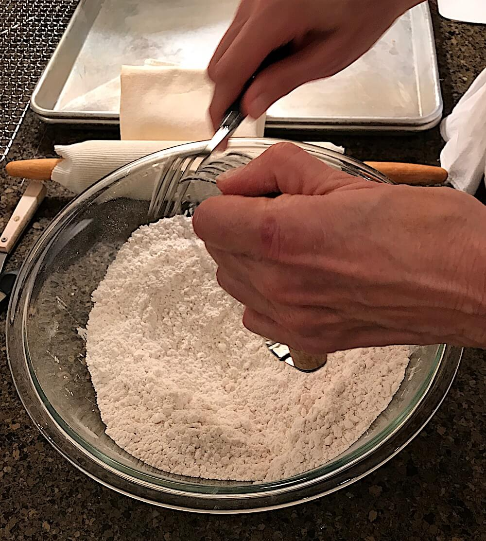 Cut in the Crisco with a pastry blender until the mixture has lumps the size of peas.