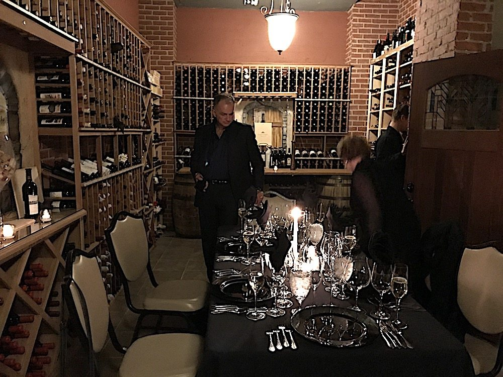 Friends Tim Young and Monique Anderson checking out the charming table set up for dinner in the wine cellar of Cherokee Country Club.